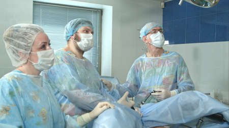 Team of doctors working together during a surgery in an operating room at a hospital