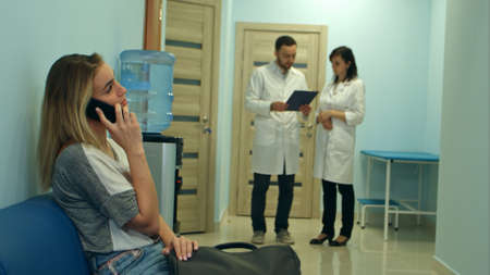 Female patient talking on the phone in hospital hall while two doctors consulting Stock Photo
