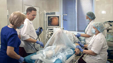 Doctors conducting procedure in endoscopy room
