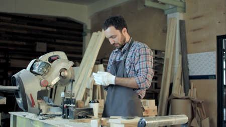 Carpenter standing near electric saw in his workshop and drinking coffee. Banco de Imagens