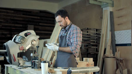 Carpenter with beard makes something on his smart phone in workshop.