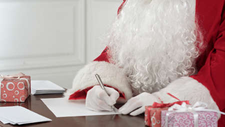 Santa Claus answering Christmas letters sitting at his table