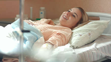 Young female patient lying in hospital bed on drip talking to a doctor