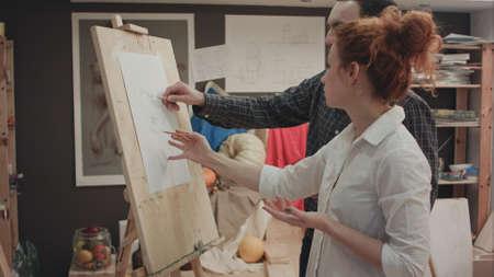 Female art teacher explaining student how to measure face proportions