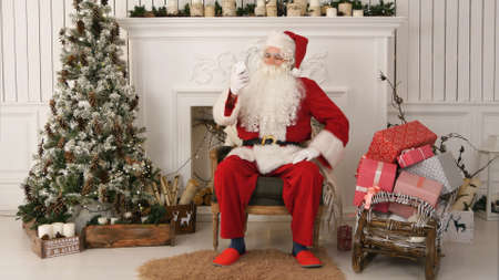 Happy Santa Claus reading Xmas messages on the phone and smiling while sitting at his chair