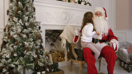 Sweet little girl sitting on Santa lap and describing him what she wants for Christmas