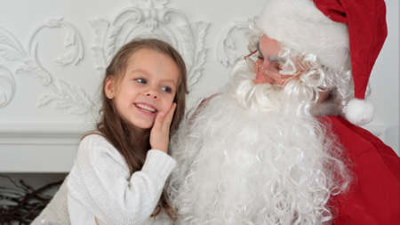 Sweet little girl on Santa Claus lap telling him what she wants for Christmas