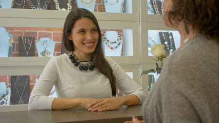 Young female seller meets and listens to buyer who just comes to jewelry shop
