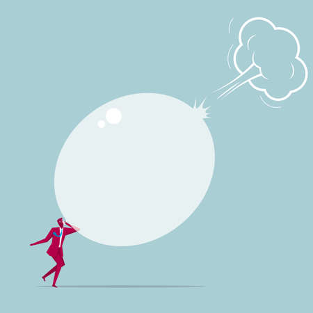 Businessman blowing a bursting balloon. Isolated on blue background.