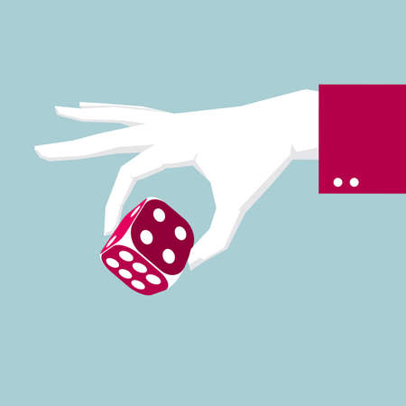 Fingers take the dice. Isolated on blue background.