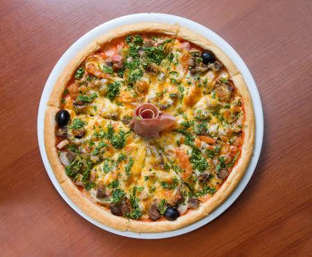 Tasty Italian pizza with ham on wooden table