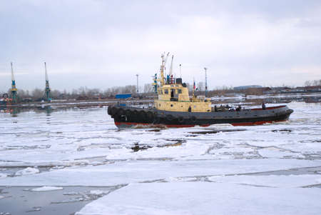 Tug and driving of ice on river.Spring river photo