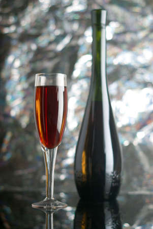 Bottle and glass of red wine  on brilliant backround photo