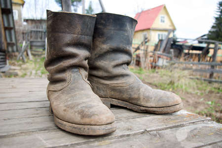 old muddy farmers boots on background wooden wall Stock Photo - 3199398