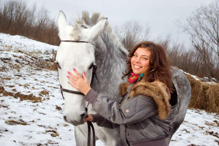 beautiful girl-gypsy with horse.winter landscape photo