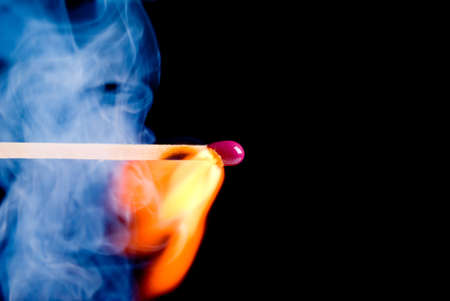 Burning match with blue smoke over black background photo