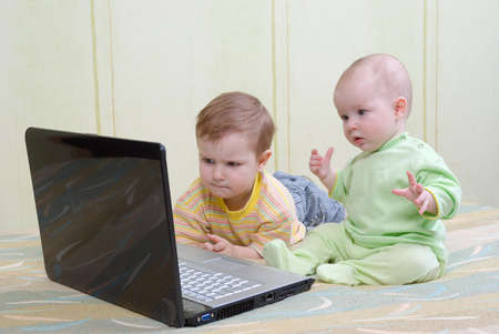 Little girl and boy using laptops.viewing the baby film