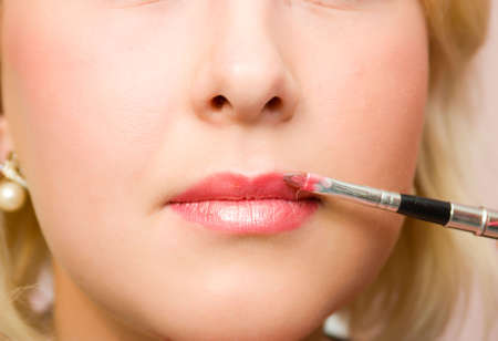 visagiste: Which girl of a lip paints the professional visagiste with red  lipstick. Stock Photo