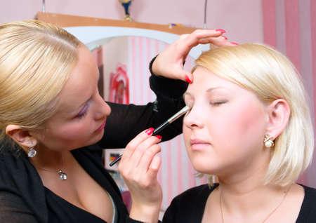 visagiste: Which girl puts shadows the professional visagiste.putting on models eye make up