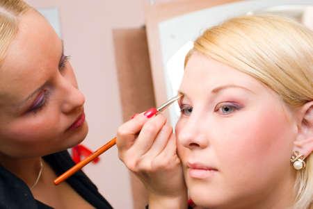 visagiste: professional  visagiste does a bright make-up.putting on models eye make up