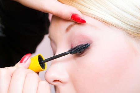 visagiste: professional the visagiste does a bright make-up.putting on models eye make up