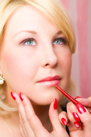 visagiste: Which girl of a lip paints  professional visagiste  red  lipstick. Stock Photo