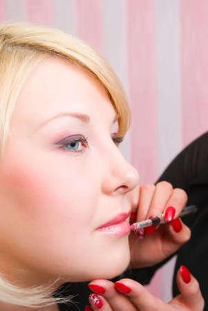 visagiste: Which girl of a lip paints professional visagiste pink lipstick Stock Photo