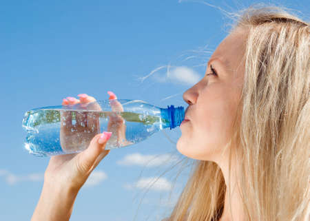 Beautiful blond girl drinking water under blue sky
