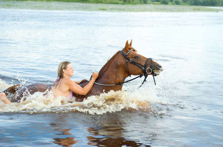 young woman swimming winth  stallion in river photo