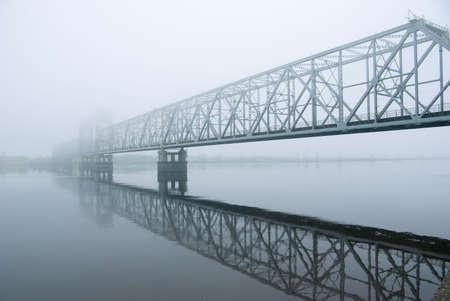 railroad crossing: railway bridge through the river.matutinal mist