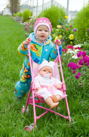 flowerses: baby with doll on walk.on lawn with flowerses