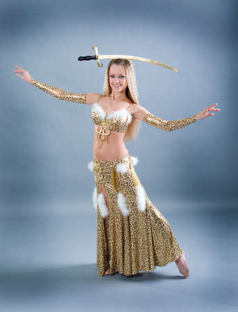 Attractive woman performing arabic dance with sabre photo