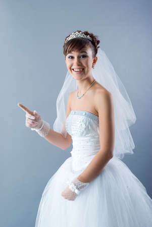 Beauty young bride dressed in elegance white wedding dress  gray studio background  photo