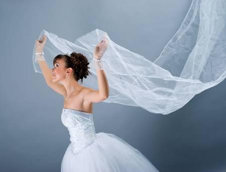 Beauty young bride dressed in elegance white wedding dress  gray studio background Stock fotó - 6360129