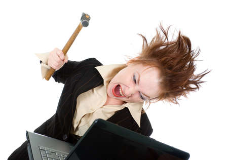 angry and stressed businesswoman smashing her laptop with a hammer  photo