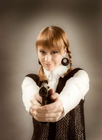 blonde holding a gun and aiming toward camera, focus on gun  Stock Photo - 6533967