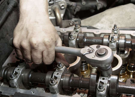 machine part: Repair of the engine. A hand with the tool. Automobile service