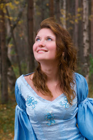Very beautiful girl in medieval dress in autumn wood. photo