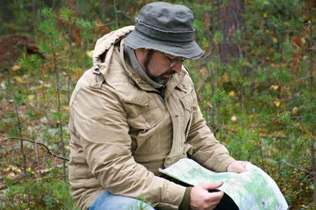 Hiker with map in forest .boondocks -taiga photo