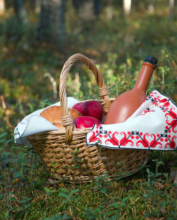 Picnic wicker basket with patty, food and wine bottle in wheat field  photo