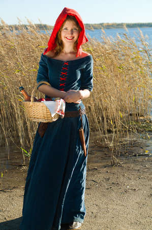 red Riding  hood standing beside lake . beautiful girl in medieval dress Stock Photo - 7955540