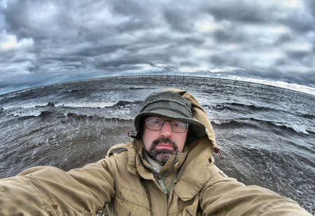 man-fisherman on background Big ocean wave breaking the shore Stock Photo - 8172502