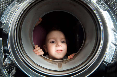 boy peer into get old washer .Closeup photo