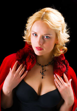 Sexy model wearing winter fur red  coat on  black  background  photo