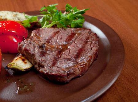 carne asada: Carne a la parrilla en plato blanco con verdura