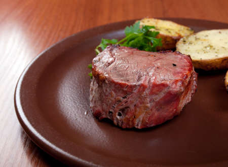 Grilled beef on white plate with potatoes salad and tomatoes  .Shallow depth-of-field.  photo