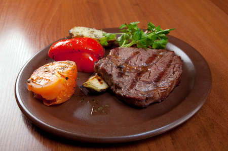 carne asada: Carne a la parrilla en plato blanco con verdura. Close-up