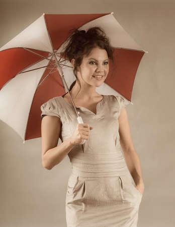 mini umbrella: sexy brunette girl with umbrella  on  gray background