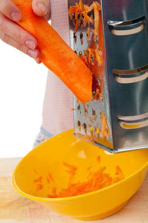 Mano rallador de cocina de alimentos vegetales de zanahoria.Fondo de estudio, blanco.  Foto de archivo - 9074485