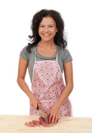 beautiful housewife cutting meat. Studio, white background.  photo